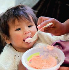 A mother feeds her child fortified porridge in Bolivia