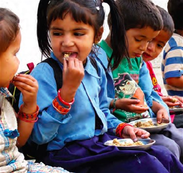 Primary school students receive nutritious mid-day meals of fortified wheat-soya, in Nepal
