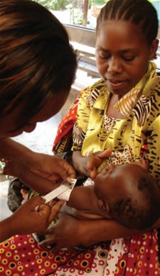 Measuring MUAC of an infant, Kilifi County Hospital, Kenya