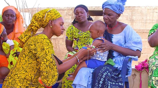 A community health volunteer monitors growth by measuring a child's mid upper arm circumference (MUAC) in Matam, Senegal