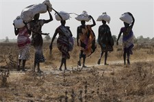 Women carry sacks of aid food in Thonyor, Leer county, South Sudan