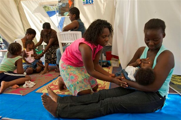 A nurse reviews with a mother how best to breastfeed her daughter in a baby-friendly tent in Haiti