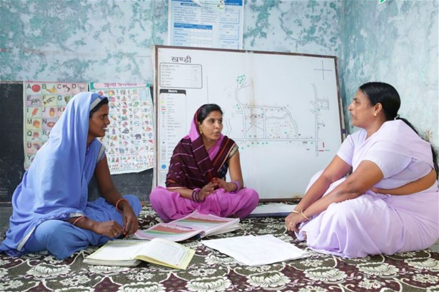 Meeting of all three community health and nutrition workers in Khandi village, Rajasthan, with village map in background
