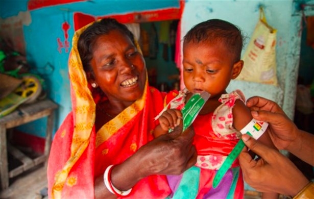 A child's MUAC is measured as her grandmother holds her by the CMAM District Coordinator Sudhakar, Bokaro, India, 2017