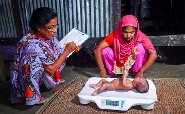 Field research officers measure the weight of an infant under six months in Barisal, Bangladesh, 2016