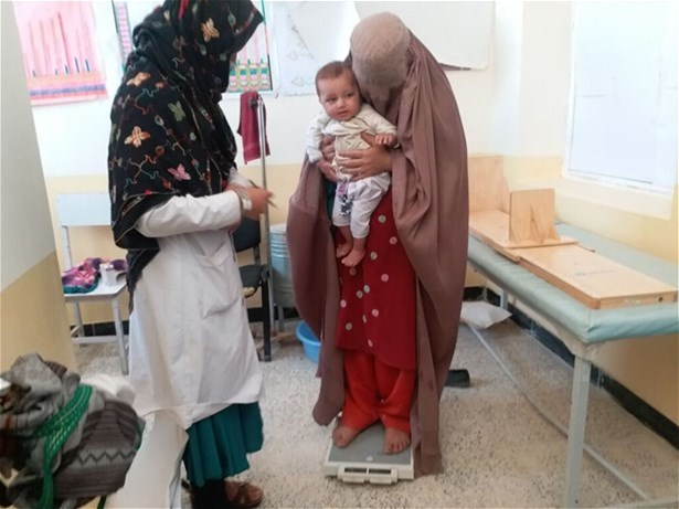 A nutrition counsellor weighs a mother and child at a health clinic in Zabul province