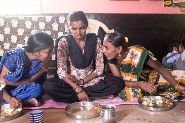 Pregnant women enjoying a hot meal and conversation in the Mathrupoorna scheme