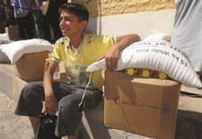A Syrian boy collects his family's monthly ration of rice, flour, pasta, beans, vegetable oil, sugar and yeast.