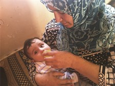 After receiving individual counselling, a woman is cup feeding her child with expressed breastmilk