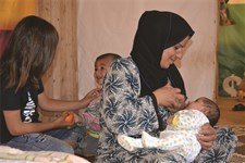 A Syrian refugee mother successfully breastfeeds her child after receiving individual counselling from an IOCC lactation consultant