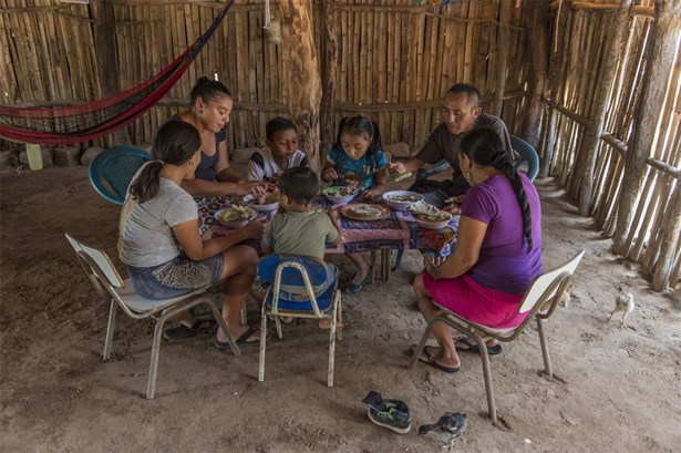 A family shares a nutritious meal of chicken soup: however, rural poverty in El Salvador often results in lack of dietary diversity.