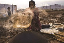 A Syrian mother from Homs, Syria bakes bread outside her shelter in Turbide, Bekaa, Lebanon