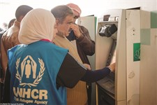 UNHCR staff assisting Syrian refugee with their first-time access to cash assistance through iris scanning, Mafraq, Jordan.