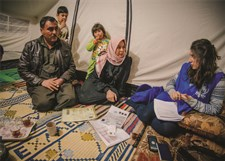 A Syrian refugee family tells a UNHCR staff member about life in a tented settlement.