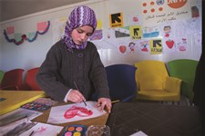 A Syrian refugee girl paints at a children's play area at an IRC women's center at Zaatari camp.