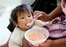 A mother in Bolivia feeds her child porridge fortified with micronutrient powders
