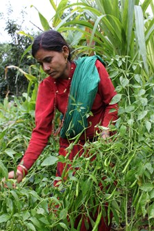 A farmer assisted by the project shows her vegetable garden