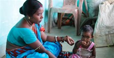 Binata Mahanta, a rural farmer in Bhandariposi Village Odisha, India, feeds her 2 year old daughter with complementary foods she learned about during a SPRING-Digital Green community video screening on infant and young child feeding practices.