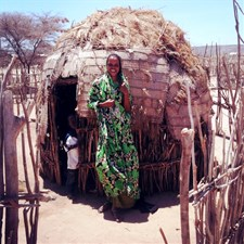 Woman in front of a manyatta (a Masai or Samburu settlement)